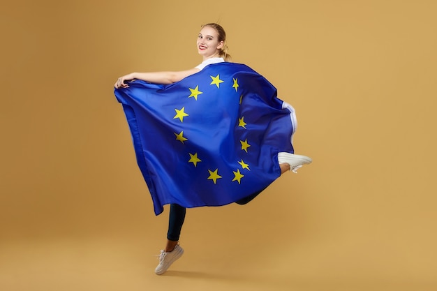 Attractive blonde made a jump with the flag of the european union. photo shoot in the studio on a yellow background.