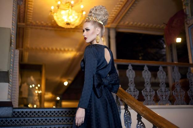 헤어 스타일이있는 매력적인 금발 모델, 왕관과 값 비싼 귀걸이, 드레스 '활의 뒷모습