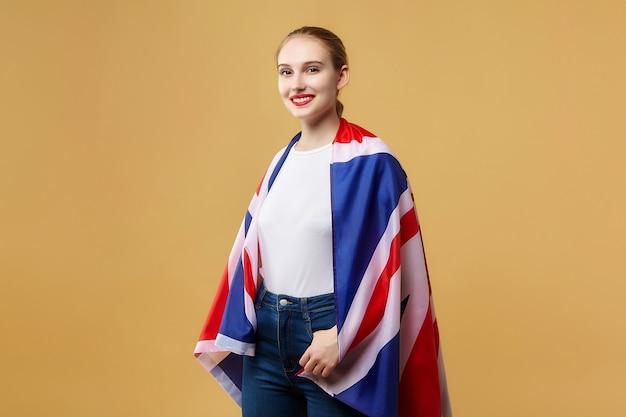 Привлекательная блондинка позирует с британским флагом. фотосессия в студии на желтом фоне.