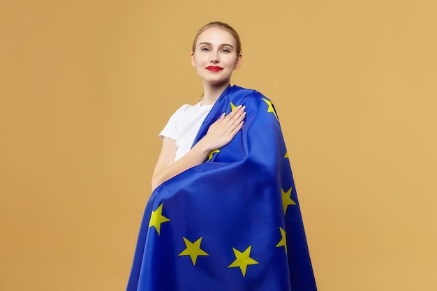 Attractive blonde poses with the flag of the european union. photo shoot in the studio on a yellow background.