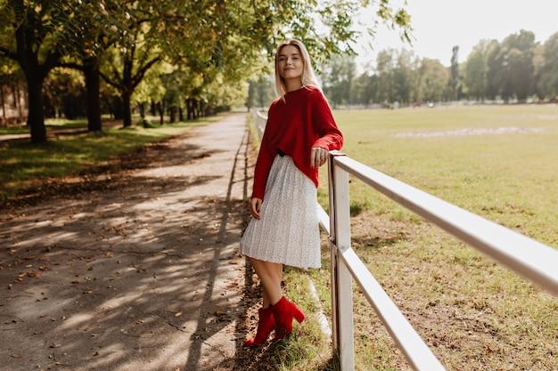 秋の公園でスタイリッシュな赤い服を着てポーズをとる魅力的なブロンド。屋外で楽しい時間を過ごしている白いドレスを着ているかわいい女の子。