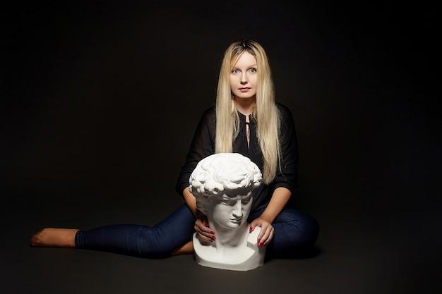 Привлекательная блондинка позирует с бюстом давида. фотосессия в студии на черном фоне