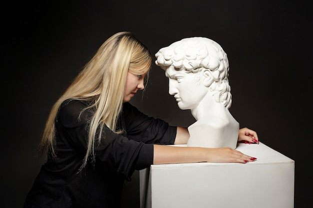 Attractive blonde posing with a bust of david. photo shoot in the studio on a black background