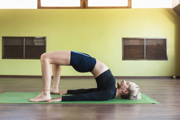 Attractive blonde in sports shorts and rashguard practicing yoga doing dvipada pithasana half bridge pose