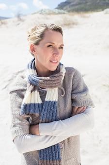 Привлекательная блондинка, стоя на пляже в шерстяном шарфе
