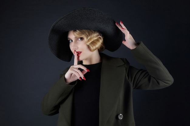 검은 모자에 복고풍 헤어 스타일을 가진 매력적인 금발이 그녀의 입술에 손가락을 눌렀습니다.