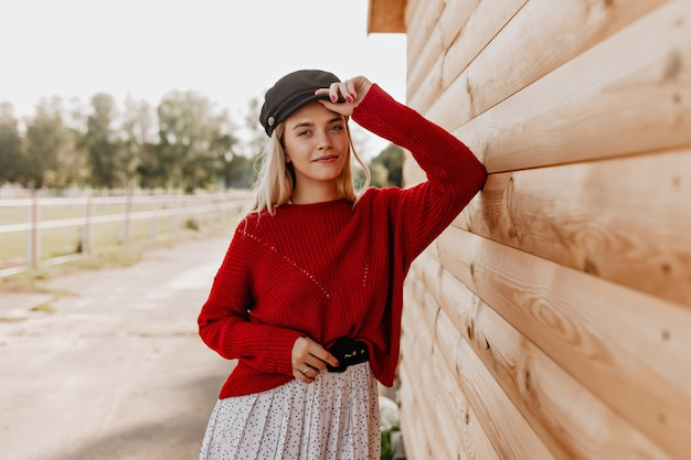 Attractive blonde with natural makeup looking with tenderness . young woman in red pullover and stylish hat posing near the wooden house.