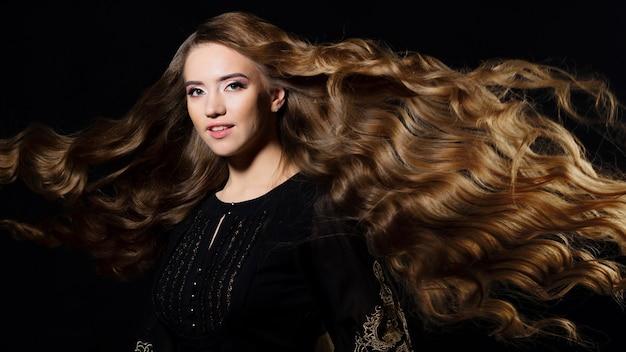 Привлекательная блондинка с очень длинными волосами, волнистыми волосами, развевающимися на ветру