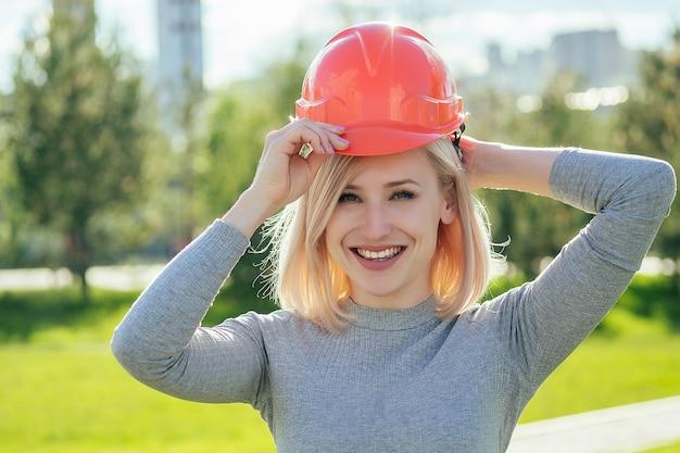 緑の芝生の背景に公園でオレンジ色のヘルメットの魅力的な金髪の女性ビルダーランドスケープデザイナー。