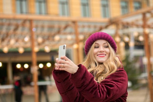 キエフの花輪の背景でselfieを作る暖かい服を着た魅力的なブロンドの女性