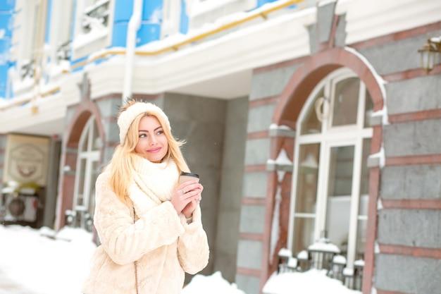 겨울 유행의 옷을 입고 거리에서 커피를 마시는 매력적인 금발 여성