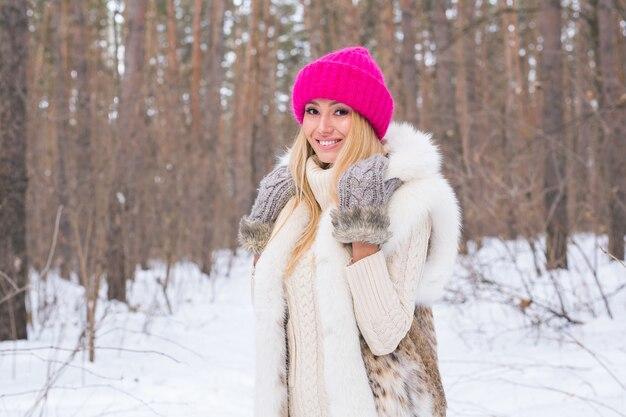 눈 덮인 숲에서 분홍색 스웨터에 매력적인 금발의 여자는 웃
