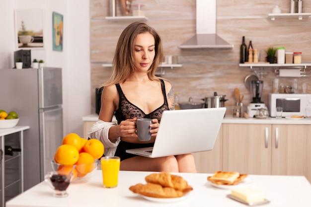 家庭の台所でラップトップを使用しながらコーヒーを保持しているセクシーなランジェリーの魅力的なブロンドの女性。下着で朝食時にタトスを持つ美しい女性。