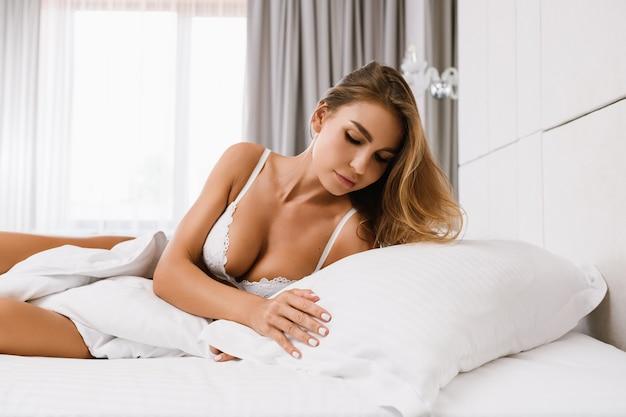 섹시한 목선이 있는 흰색 브래지어를 한 매력적인 금발 여성은 고급 아파트, 호텔 침대, 창가에서 아침 햇살에 흰색 베개를 만지고 실내에서 아름다운 생활 방식을 즐깁니다.