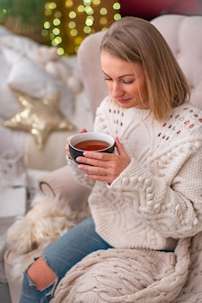 Attractive blonde woman in a knitted sweater with a cup of tea sits on the bed.