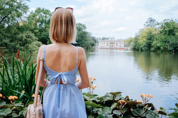 Attractive blonde woman looking at palace and lake in park in warsaw