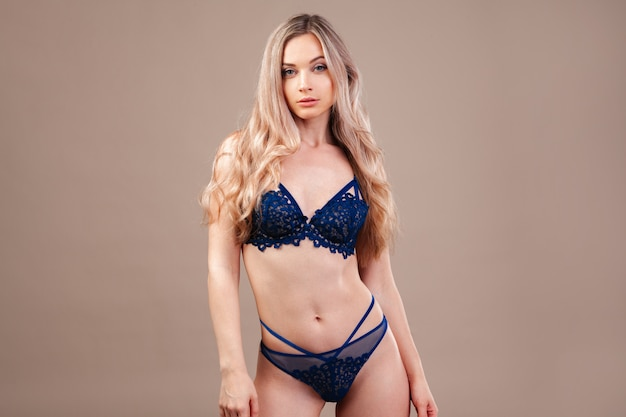 Attractive blonde woman posing in fashionable lingerie in studio