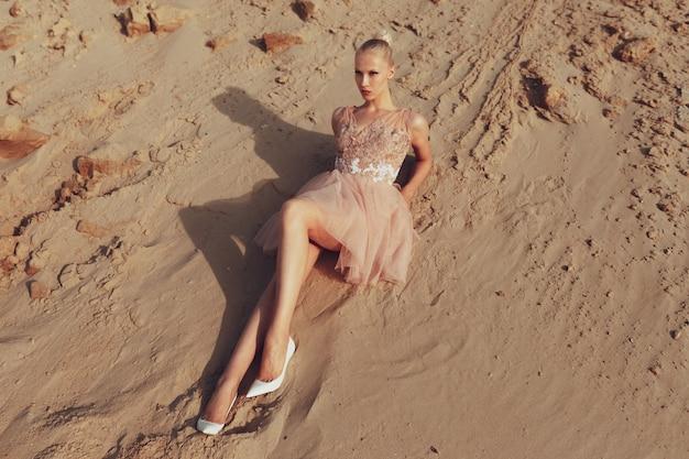 Привлекательная блондинка позирует в платье с вышивкой на пустыне, лежа на песке, в лучах заката.