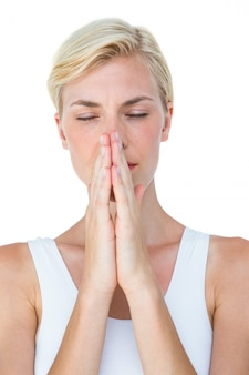 Attractive blonde woman praying on white background
