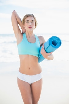 Attractive blonde woman in sportswear carrying an exercise mat