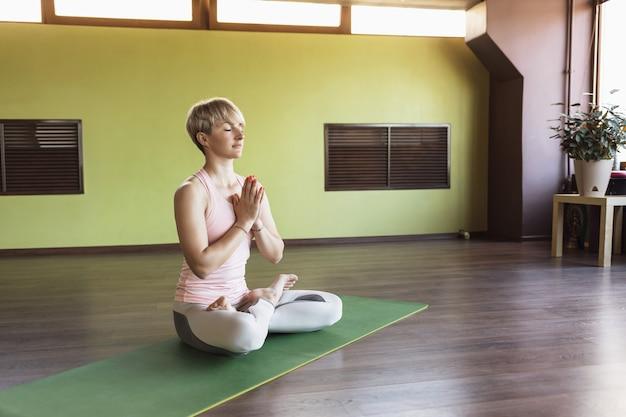 Attractive blonde woman in sportswear practicing yoga
