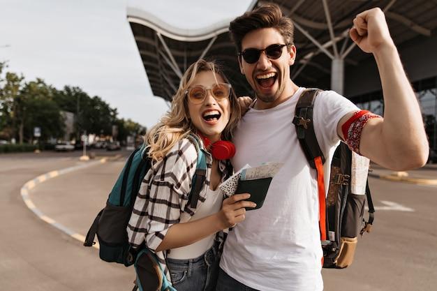 Attraente donna bionda in occhiali da sole e uomo in maglietta bianca sorride e si fa selfie vicino all'aeroporto