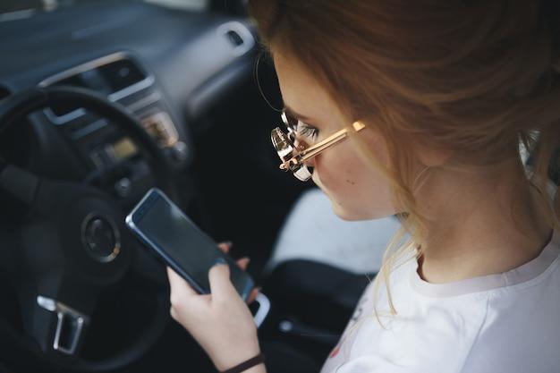 운전하는 동안 그녀의 휴대 전화에 메시징 매력적인 금발 여자 문자.