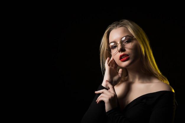 眼鏡と流行のブラウスを着て、影でポーズをとる魅力的なブロンドの女性