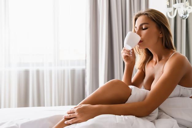 Привлекательная блондинка с красивым телом сидит в белом бюстгальтере под одеялом в светлом доме, спальне отеля, наслаждается утренним напитком в чашке перед окном.