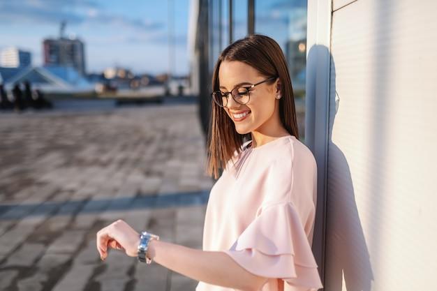 屋外に立っている間腕時計を見て眼鏡の魅力的なブロンドの女性