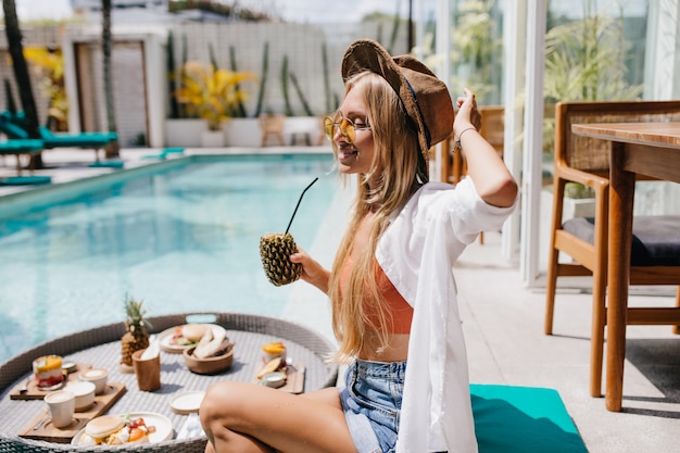 Attractive blonde woman in yellow sunglasses spending time near pool with tasty pineapple cocktail. dreamy female tourist eating fruits during photoshoot at resort.