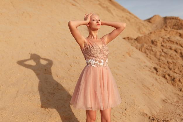 Привлекательная белокурая молодая женщина позирует в платье с вышивкой, позирует в пустыне, глядя на сторону, с закрытыми глазами, песчаный фон.