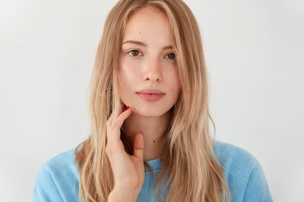 Attractive blonde young woman student with serious facial expression, thinks about passing exam