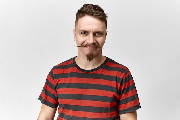 赤と黒のストライプが良い気分でスタイリッシュなtシャツを着ている魅力的な青い目のブルネットの白人男性。スタジオでポーズをとるハンドルバーの口ひげとあごひげを持つポジティブなハンサムなヒップスターの男