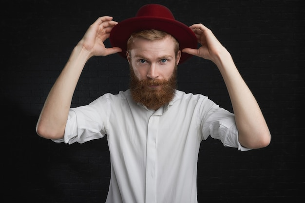 Attractive blue eyed young guy with ginger trimmed beard going to party, putting on stylish red round hat. elegant young european male in white shirt, getting dressed, taking on trendy headwear