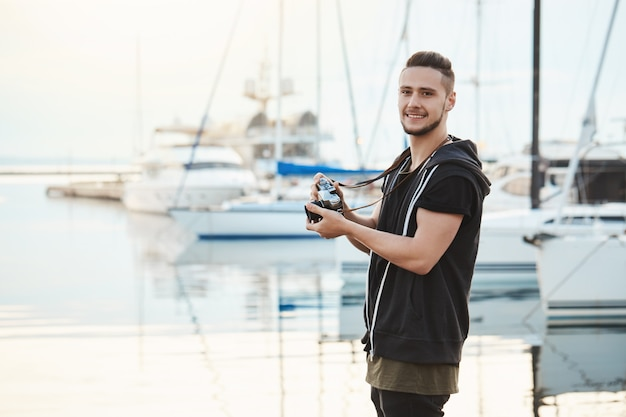 Attractive boyfriend focused on his hobby during walk with girlfriend. portrait of guy standing in harbour near yachts, holding camera, looking aside while searching for great shot.