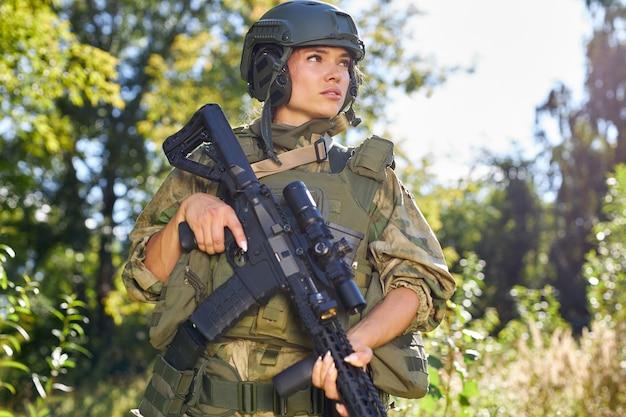 Привлекательная храбрая военная женщина с ружьем в лесу, выживание в диком лесу