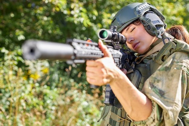 森の中で銃を持った魅力的な勇敢な軍の女性、野生の森での生存