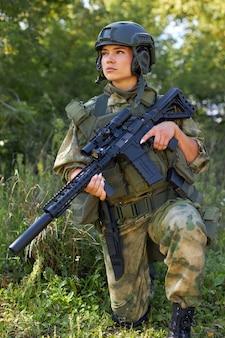 숲에서 총을 가진 매력적인 용감한 군대, 야생 숲에서의 생존