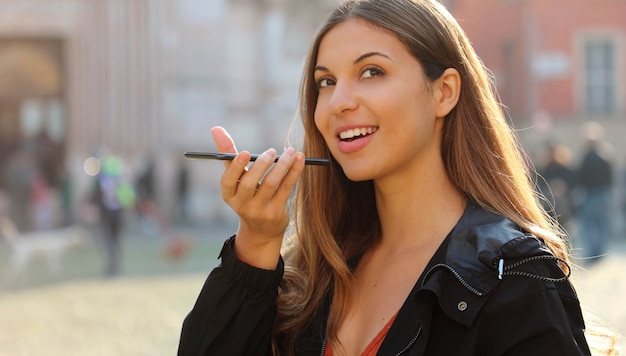 Attractive brazilian girl holding phone speaks with virtual digital voice assistant on smartphone in city street.