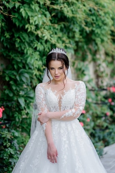Attractive bride dressed in crown with foxy sight outdoors near green leaves