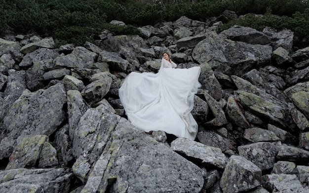 Attractive bride is standing on the huge grey rocks dressed in white ceremonial dress