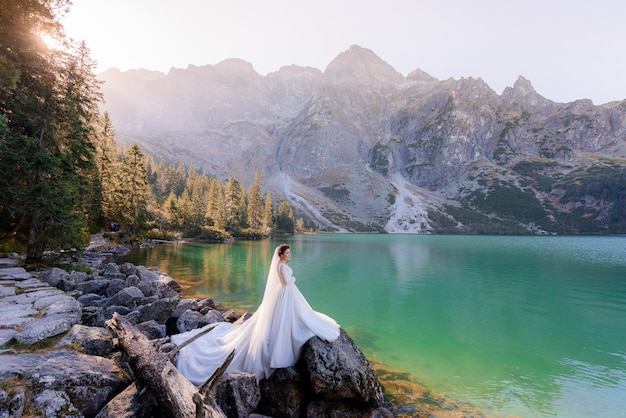 Attractive bride is standing near highland lake with picturesque view of autumn mountains
