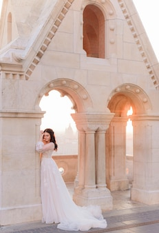 Attractive bride in  tender fashionable dress is standing near the stone column on a warm summer day