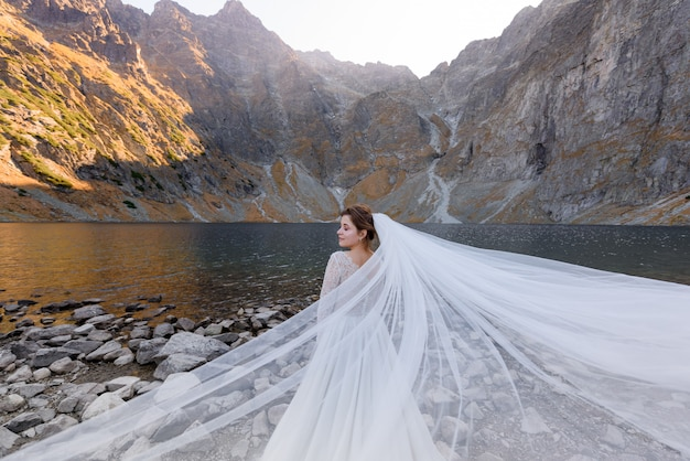 Attractive bride with closed eyes and wavy veil is standing in front of lake surrounded with autumn mountains on the sunny day