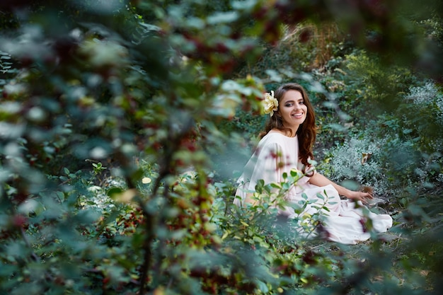 Attractive bride with long curly hair in wedding dress sitting in park, green leaves at background, wedding photo, portrait, smiling.