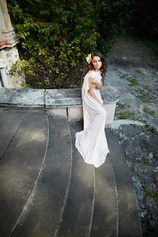 Attractive bride with long curly hair in wedding dress standing at park, wedding photo, portrait, posing.
