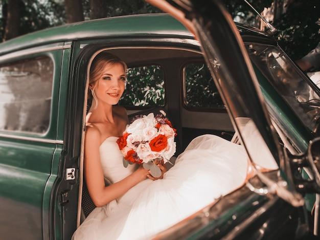 ヴィンテージカーに座っている花束を持つ魅力的な花嫁。レトロなスタイルの結婚式