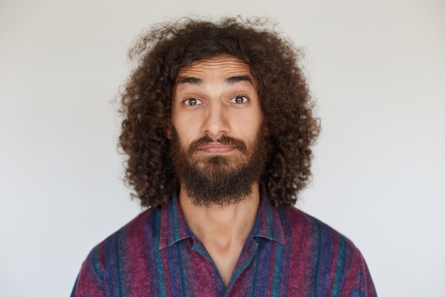 Attractive brown-eyed young bearded male with dark curly hair raising eyebrows surprisedly while looking, dressed in striped multi-colored shirt