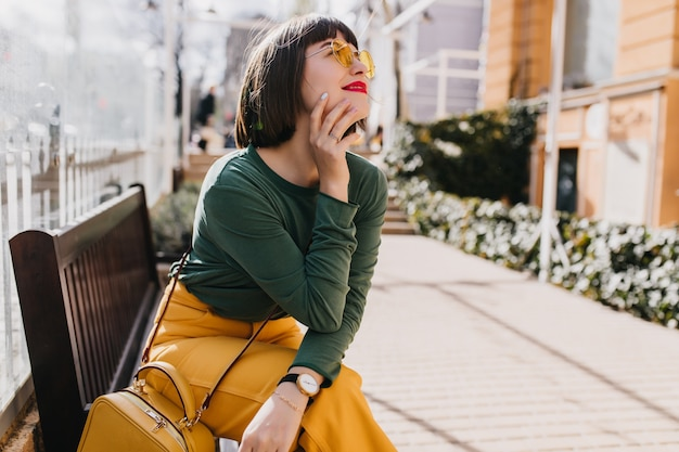 Attractive brown-haired girl in green sweater chilling on bench. outdoor portrait of gorgeous lady in sunglasses dreamy posing on the street.